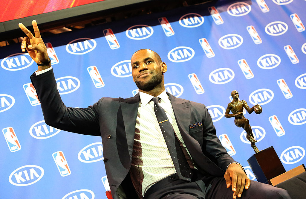 Miami Heat guard LeBron James sits by the Maurice Podoloff MVP Trophy