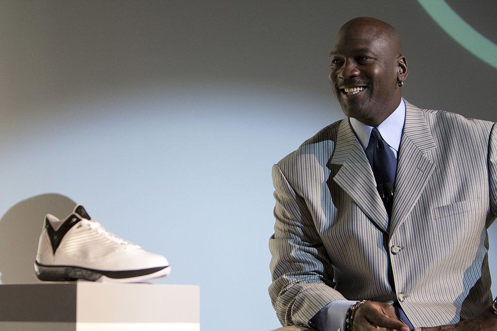 Michael Jordan poses with one of his Nike signature shoe