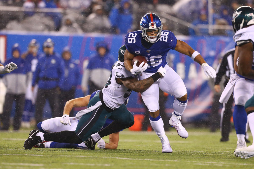 NFL running back Saquon Barkley sheds a hit from a defender