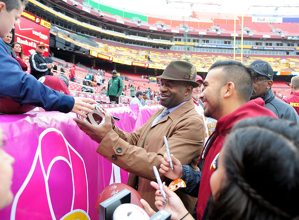 NFLPA Executive Director DeMaurice Smith signs autographs prior to an NFL game