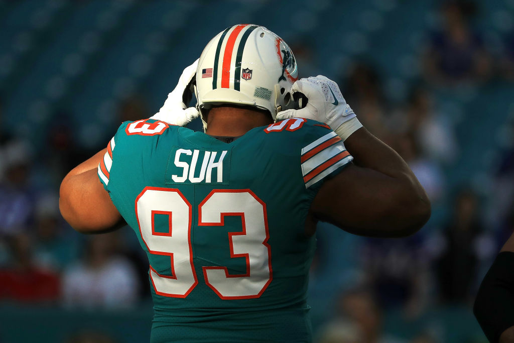 Ndamukong Suh putting on his Miami Dolphins helmet