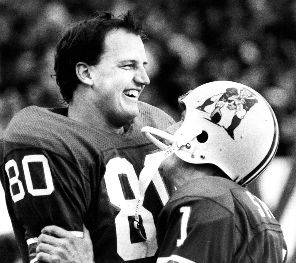 New England Patriots' Don Hasselbeck gets a hug from placekicker John Smith in a 1983 game