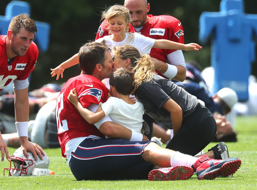 New England Patriots quarterback Tom Brady gets a group hug from his daughter Vivian, son Benjamin and his wife Gisele Bundchen following Patriots training camp in 2018
