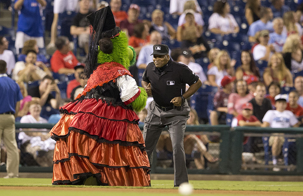 Third base umpire Laz Diaz dances with the Phillie Phantic in between innings