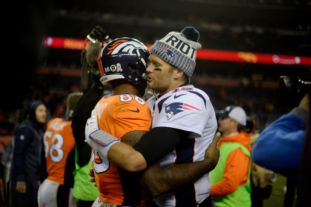 Tom Brady of the New England Patriots holds Demaryius Thomas of the Denver Broncos