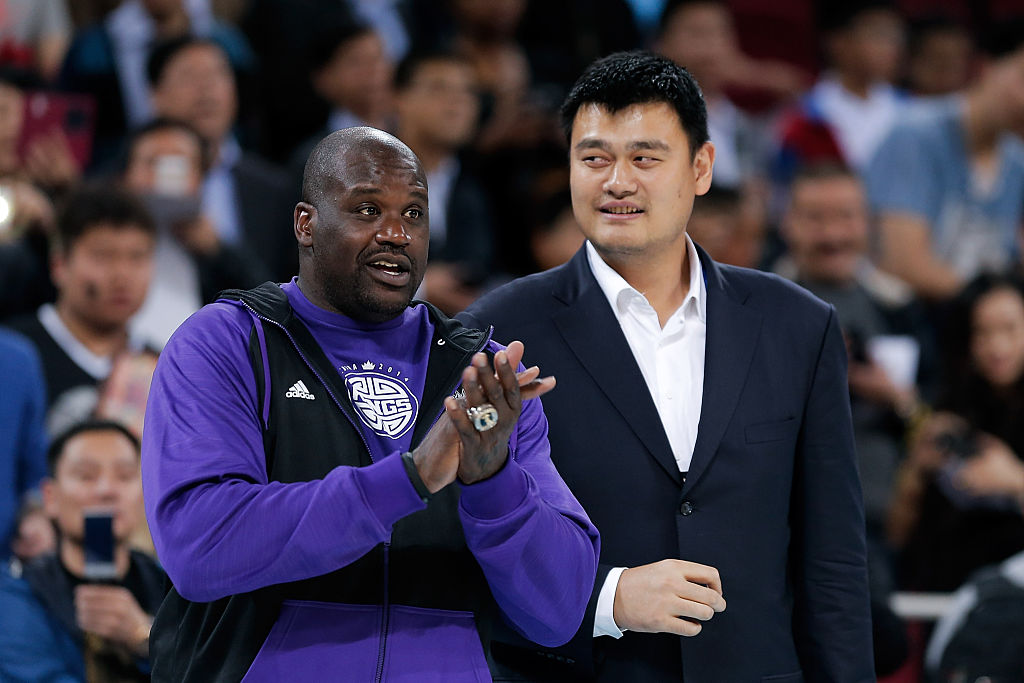 Yao Ming, former NBA basketball star, talks with Shaquille O'Neal during the 2014 NBA Global Games