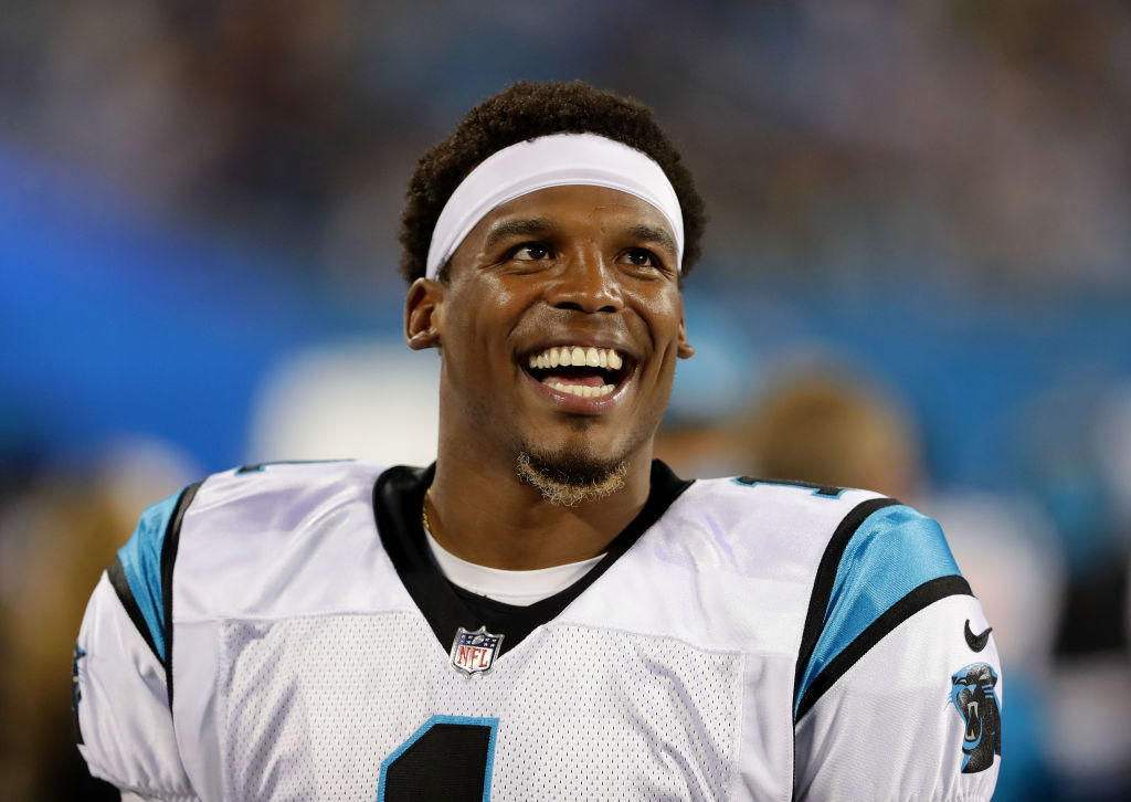 Cam Newton smiling on the sideline during an NFL game