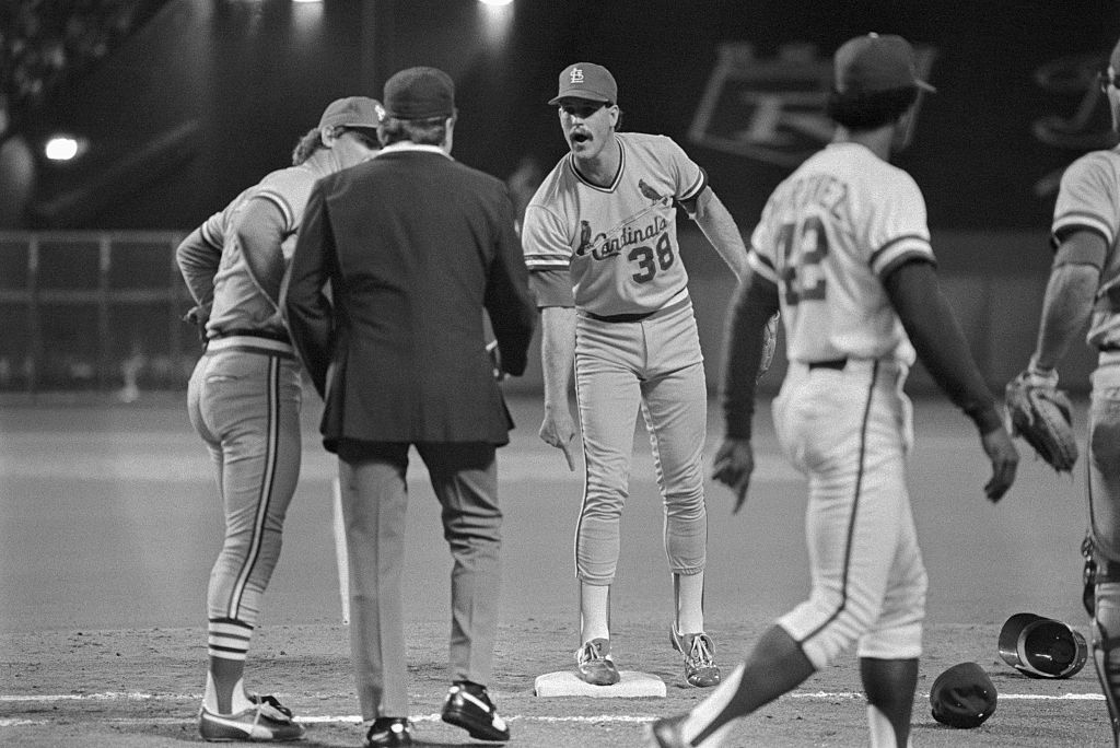 First base umpire Don Denkinger comes under attack in the ninth inning with Cardinals pitcher Todd Worrell complaining that Jorge Orta was out at first