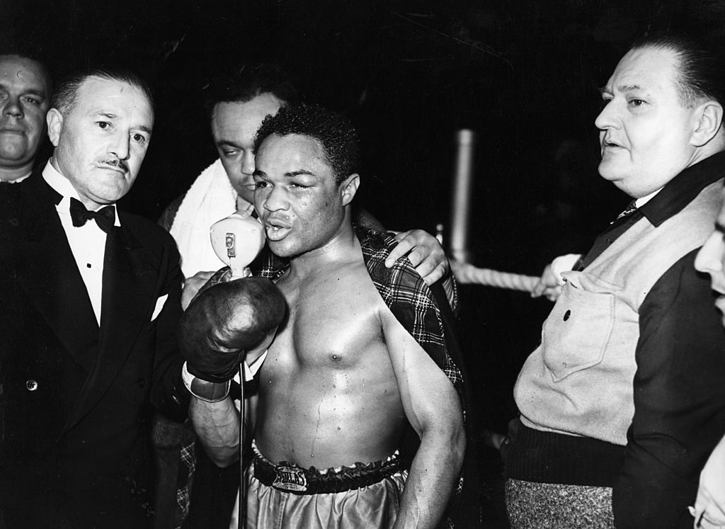 Henry Armstrong speaks into a microphone after winning a boxing match
