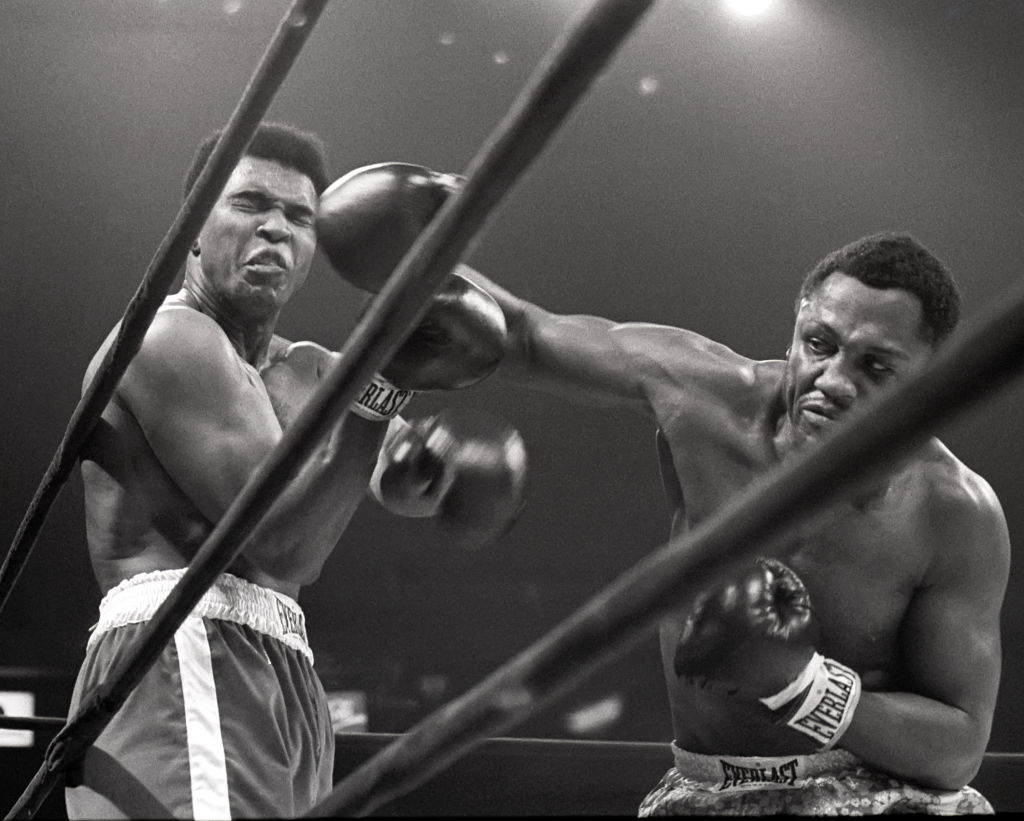 Muhammad Ali takes a hit from Joe Frazier during a match