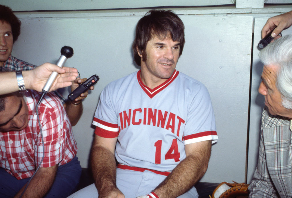 Pete Rose sitting in the dugout giving an interview