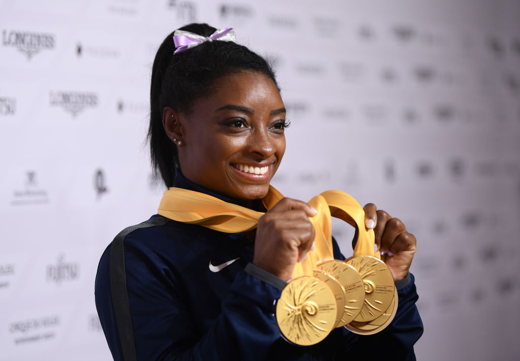 Simone Biles showing of her gold medals