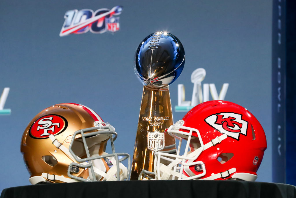 The Vince Lombardi Trophy is displayed before the Commissioners press conference with a 49ers and Chiefs helmet