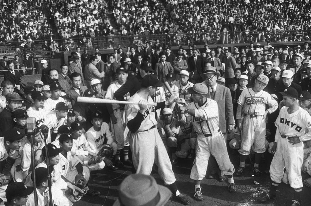 American baseball player Joe DiMaggio demonstrates batting techniques to young Japanese baseball players at Korakua Stadium, Tokyo, Japan