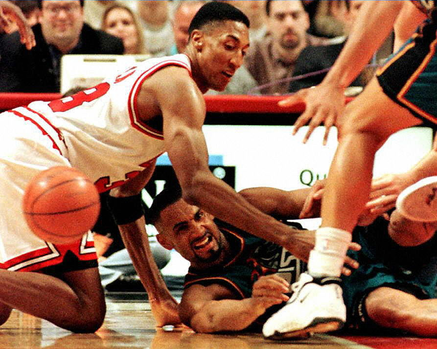 Bulls forward Scottie Pippen and Pistons forward Grant Hill scramble for a loose ball
