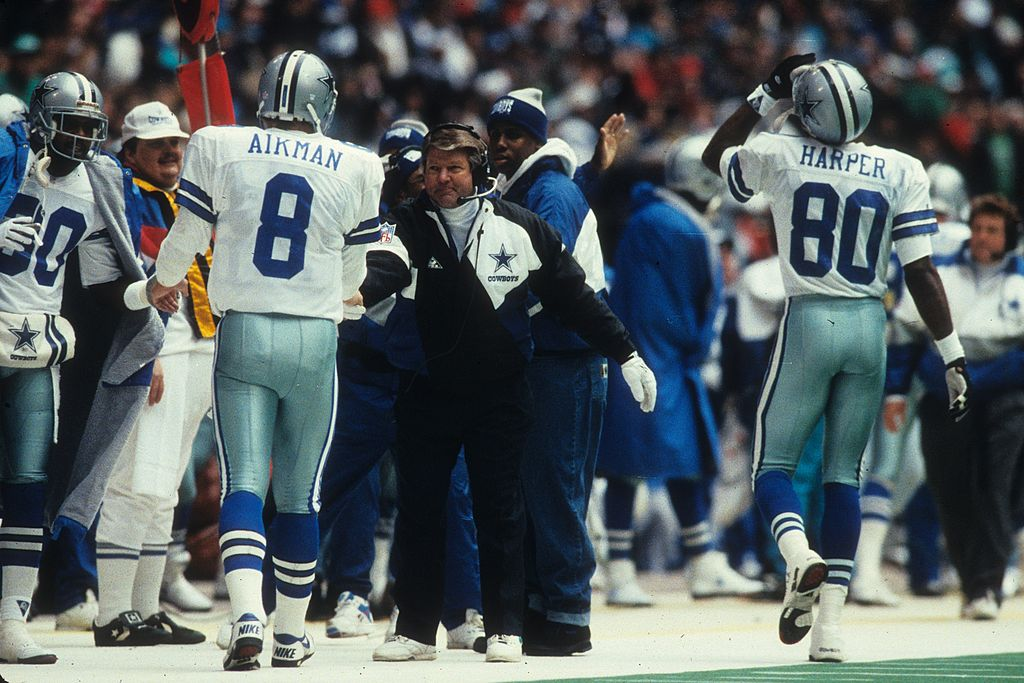 Troy Aikman and Jimmy Johnson talking on the sideline during an NFL game