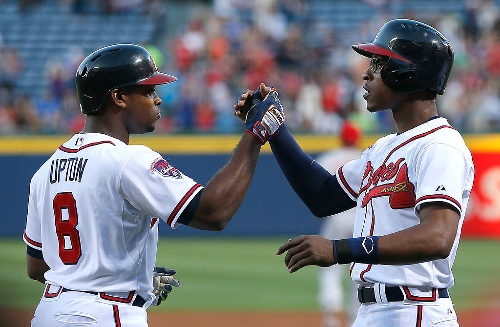 Brothers Justin and BJ Upton slap hands during a baseball game