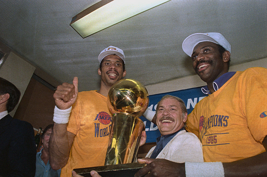 The Lakers' Kareem Abdul-Jabbar (L), owner Jerry Buss (C), and Bob McAdoo with the NBA championship trophy