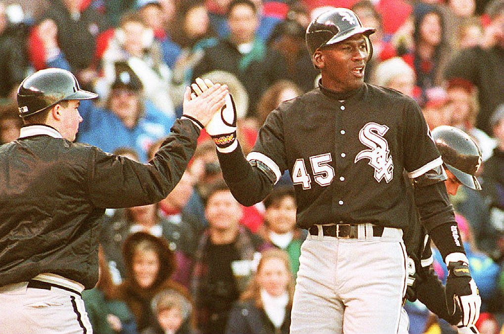 Michael Jordan high-fives a teammate during a White Sox game