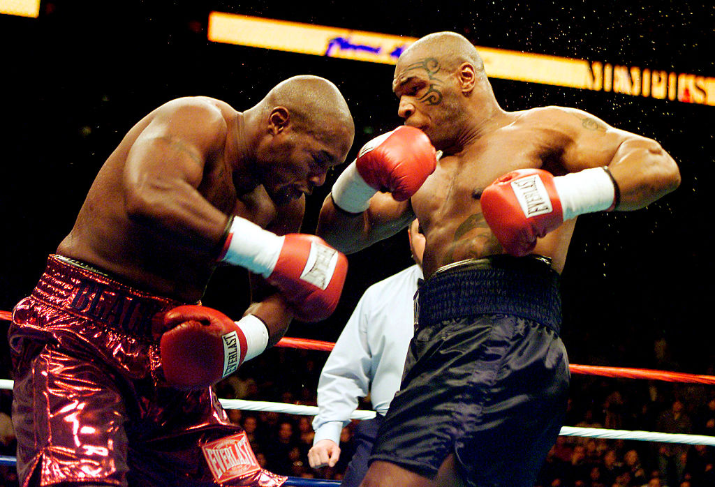 Mike Tyson (R) knocks out Clifford Etienne 49 seconds into the first round
