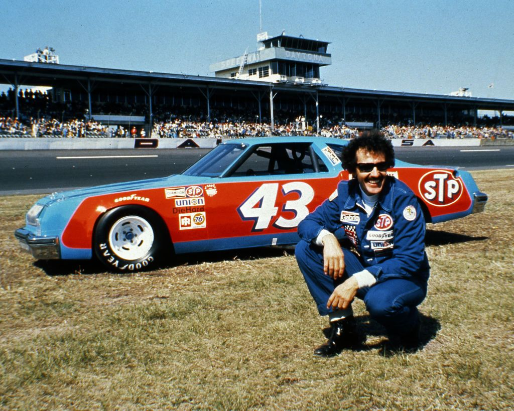 Richard Petty posing next to his car