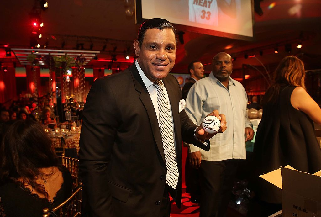 Sammy Sosa holding a baseball at a charity event