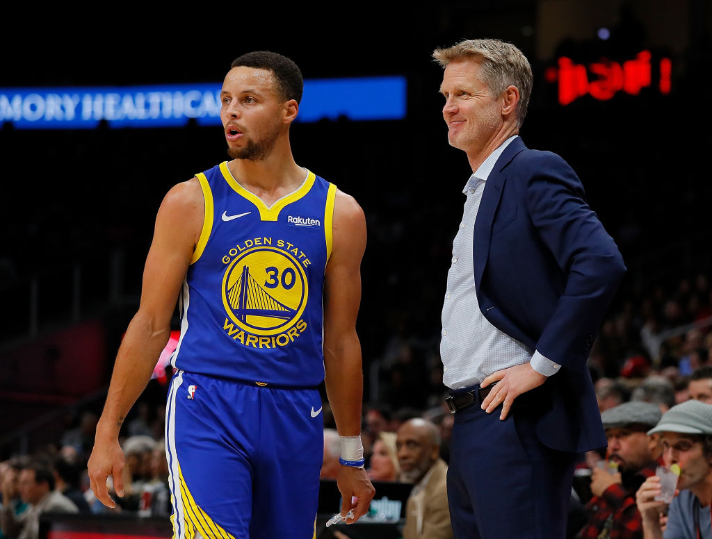 Steve Kerr and Steph Curry looking on during a Golden State Warriors game