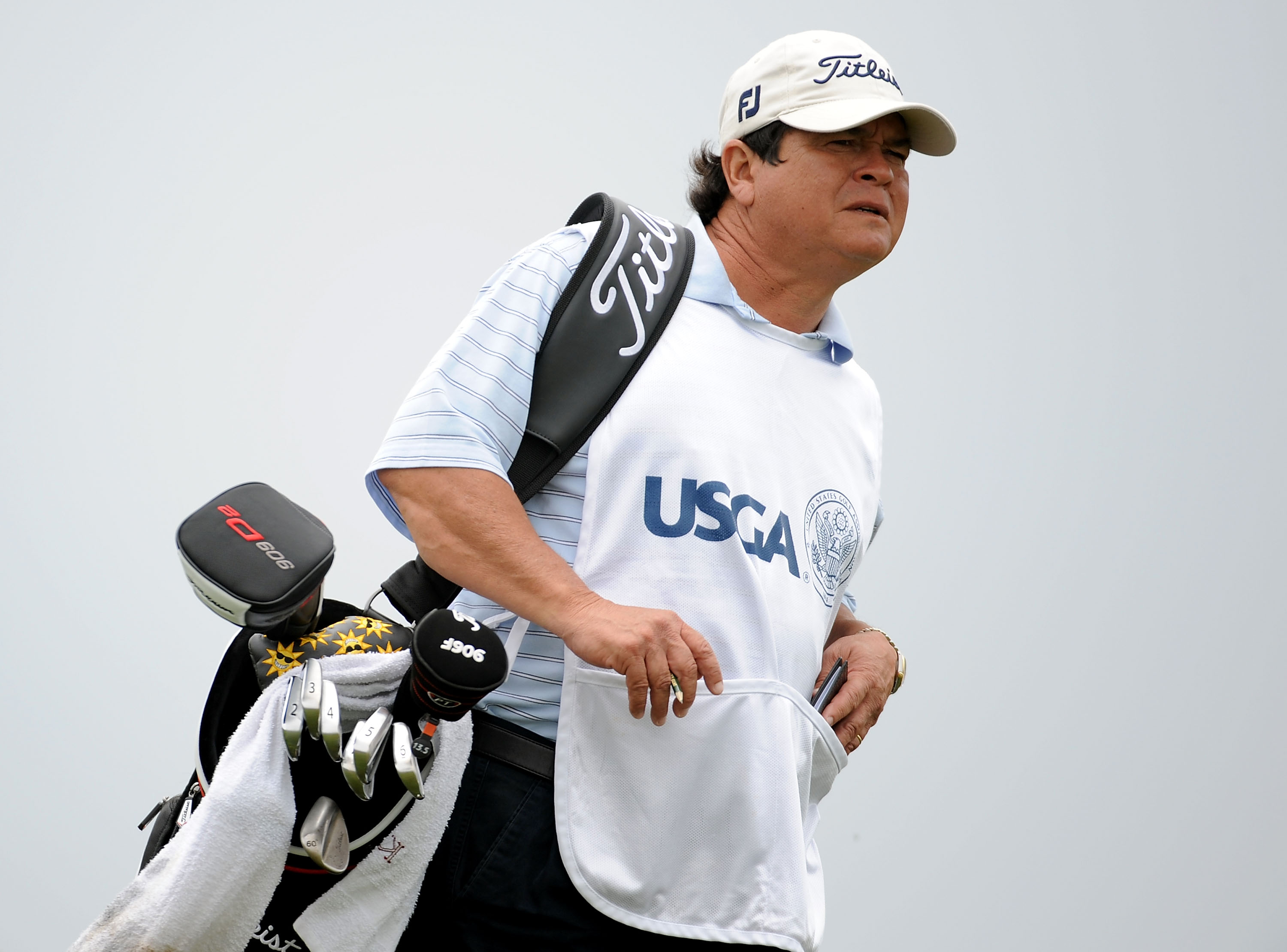 Tony Navarro walking with clubs around him during a PGA event