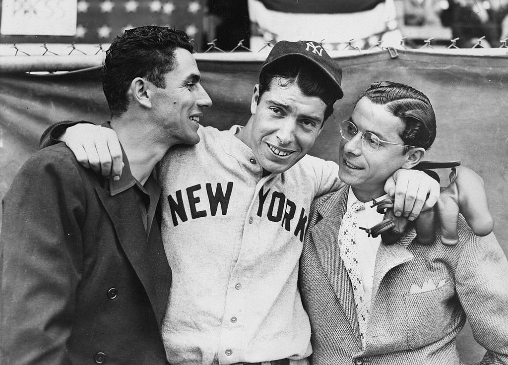 Rookie Joe DiMaggio (C) hugs his brothers Vince (L) and Dom before the start of the 1936 World Series