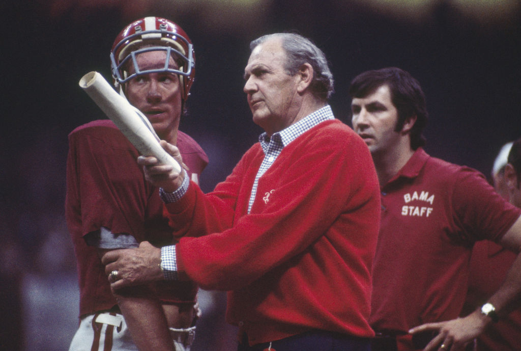 Bear Bryant talks to his team on the sideline during a game