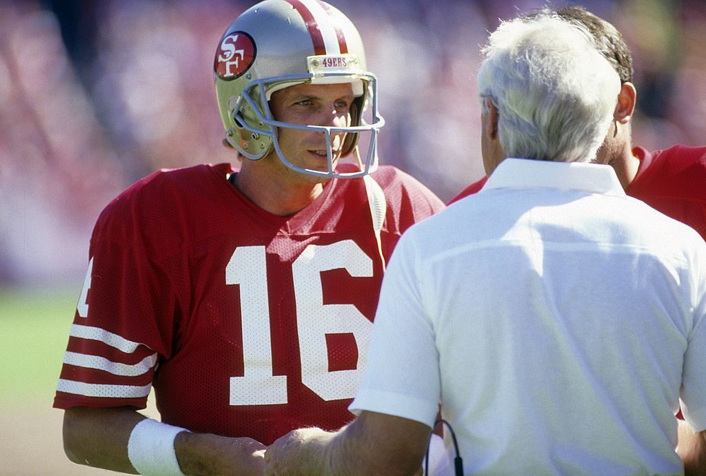 Joe Montana and Bill Walsh talking on the sideline