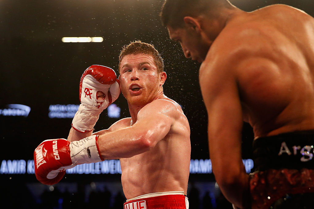 Canelo Alvarez throwing a punch at Amir Khan during their fight