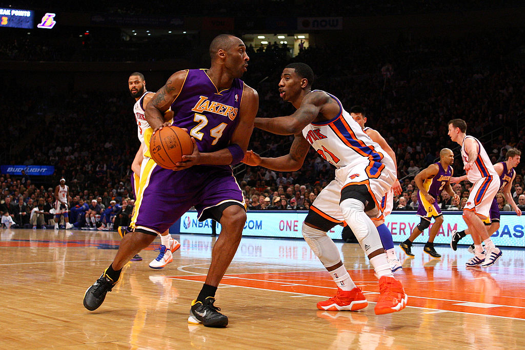 Kobe Bryant of the Los Angeles Lakers looks to move the ball against Iman Shumpert