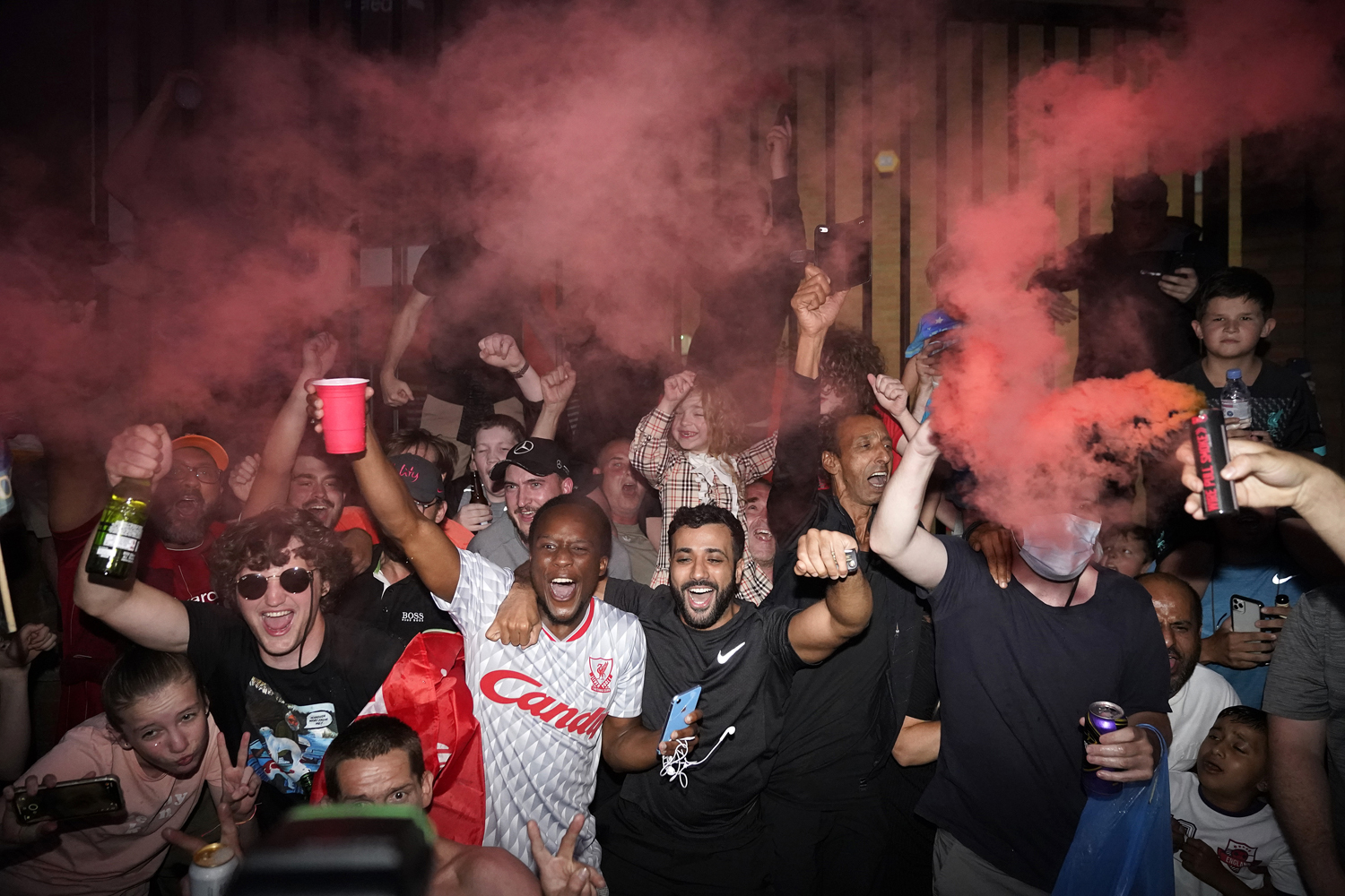 Liverpool fans celebrate Chelsea's victory against Manchester City, which ensured Liverpool of capturing its first Premier League title since 1990. | Christopher Furlong/Getty Images