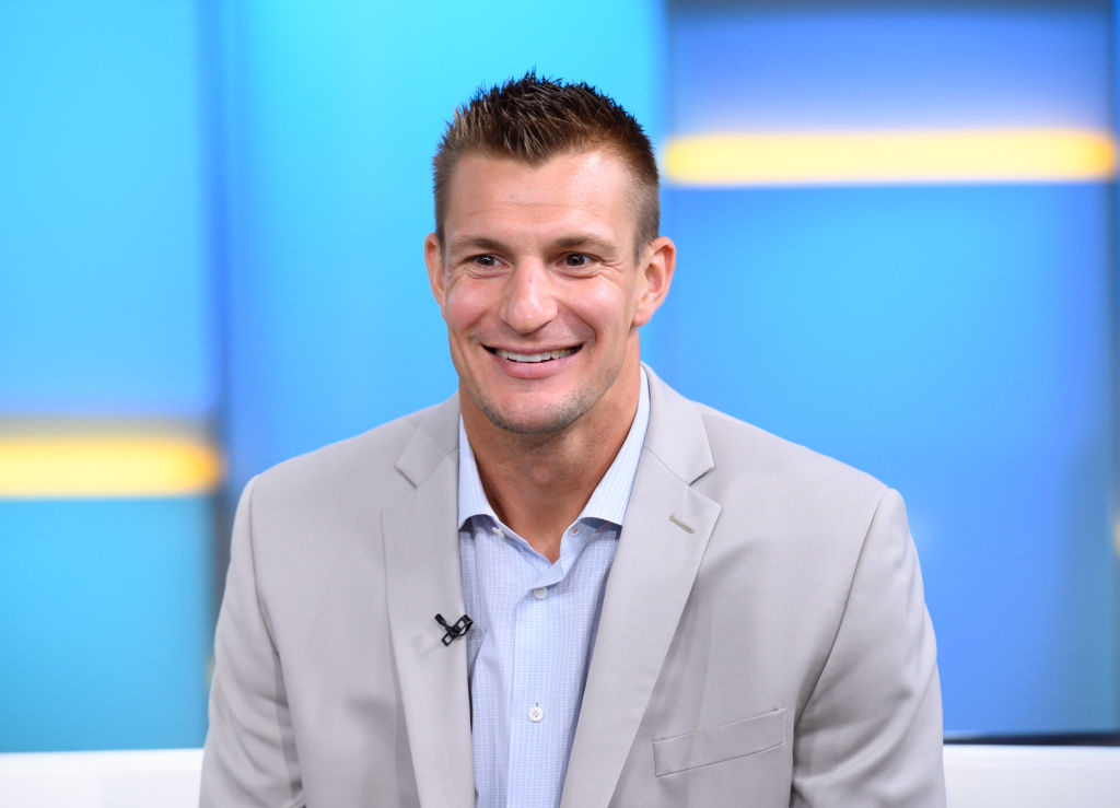 Rob Gronkowski sits in a suit on a television show