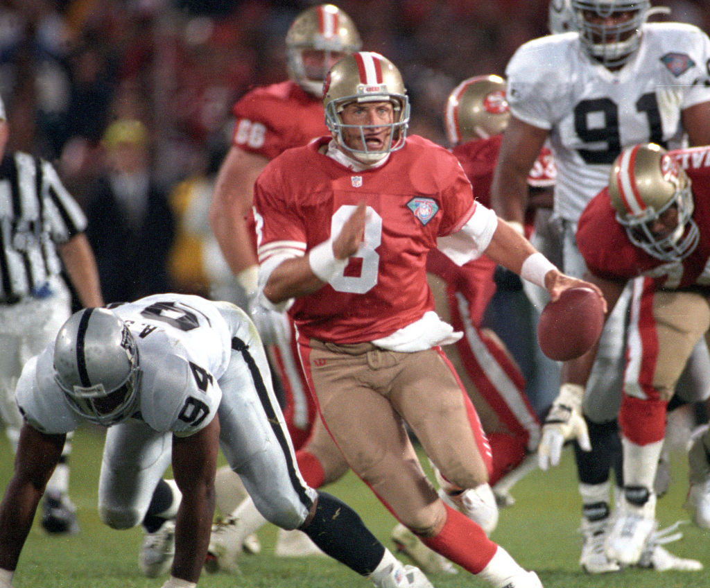 Steve Young scrambling away from defenders during an NFL game