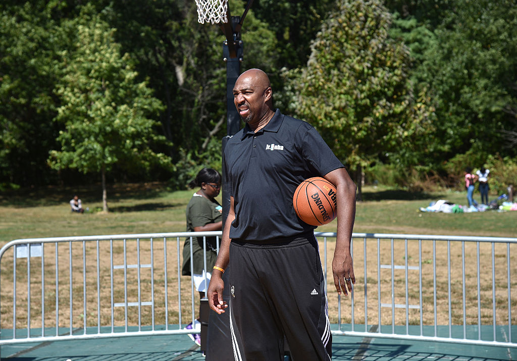 Vin Baker standing on a basketball court in street cloths