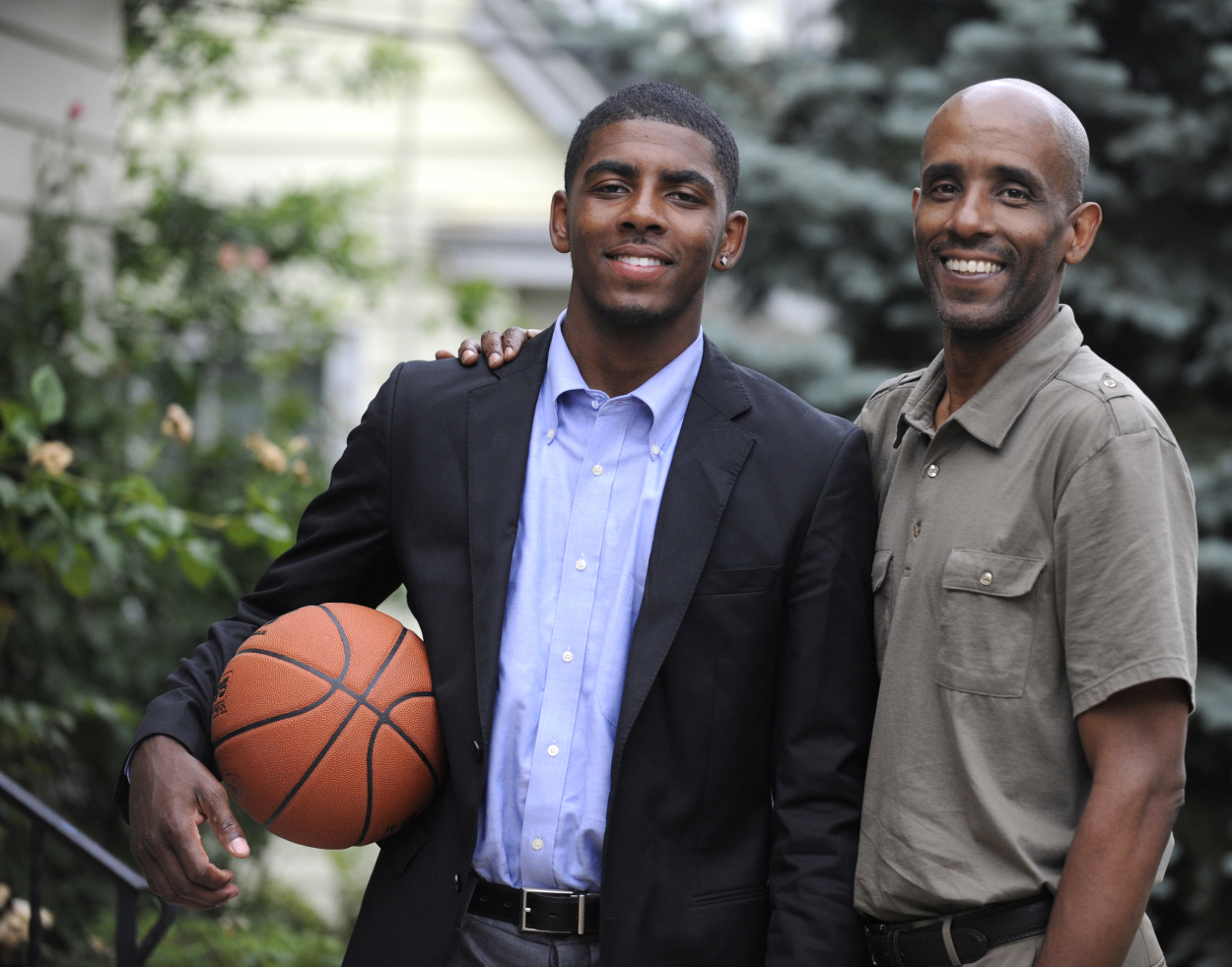 Kyrie Irving posing for a photo with his father
