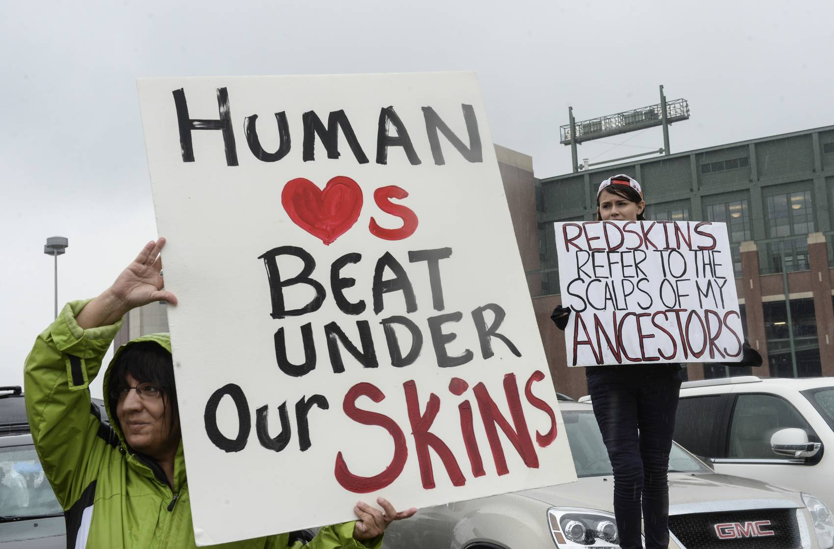 Football fans have protested the Washington Redskins' name for years. Two fans held up these signs before a Redskins-Packers game in 2013.