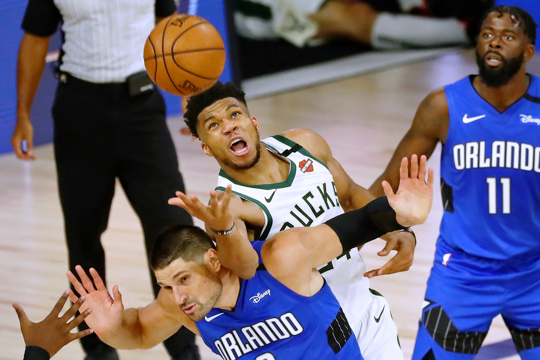 Giannis Antetokounmpo of the Milwaukee Bucks fouls Nikola Vucevic