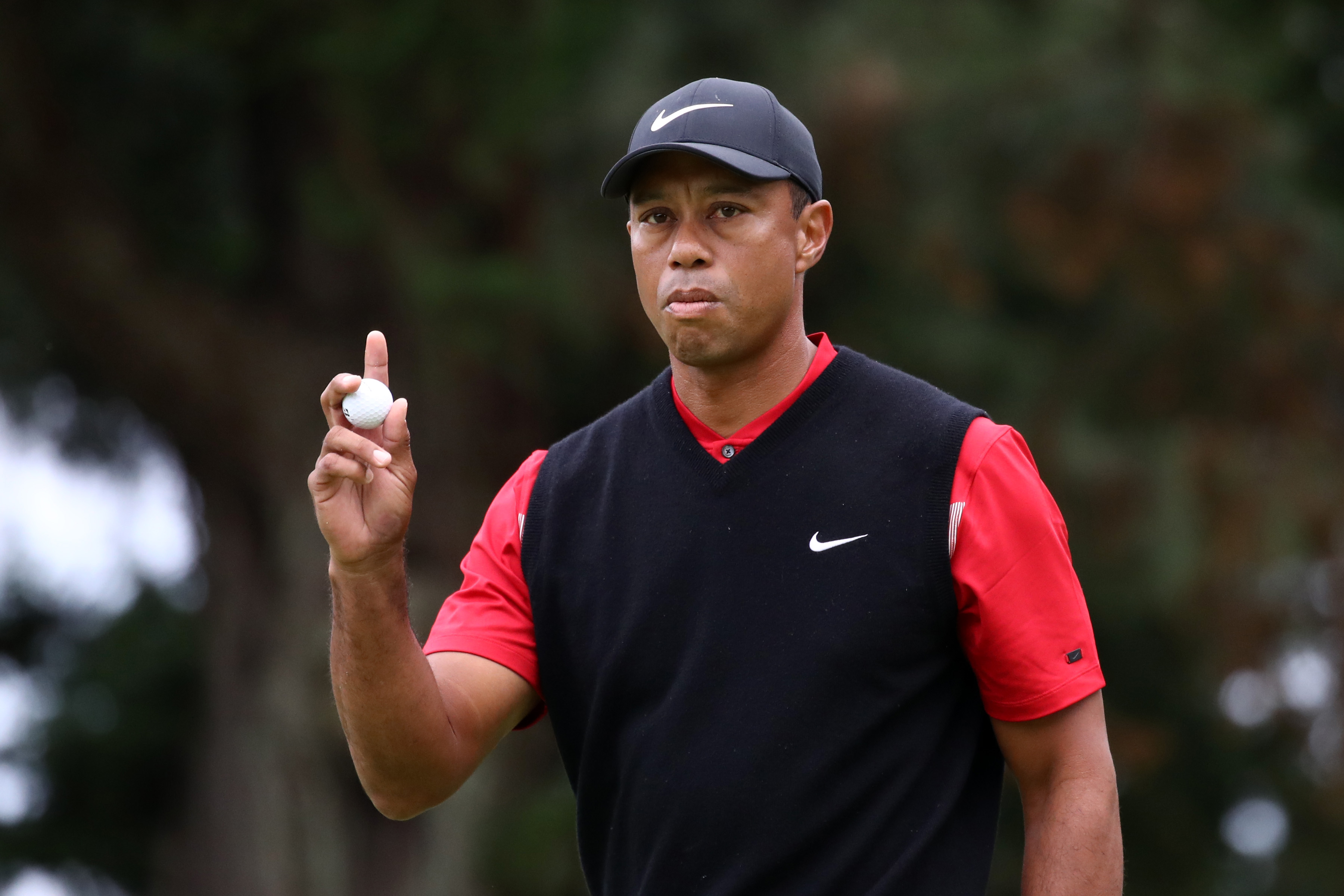 Tiger Woods waves to fans after a hole