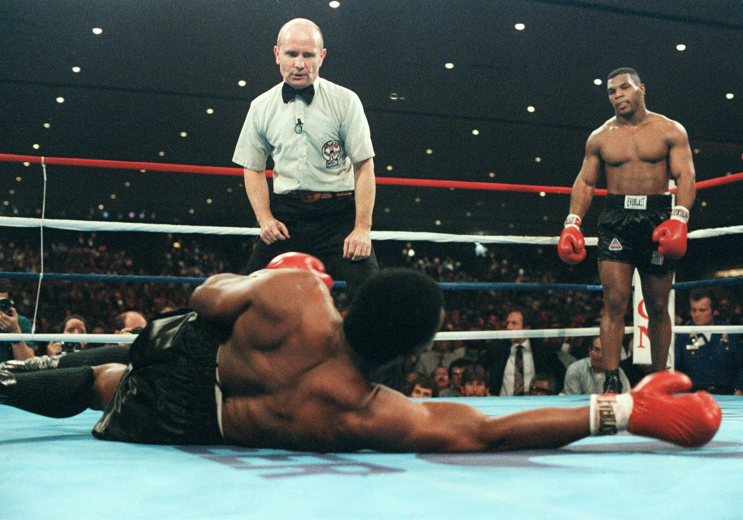 Mike Tyson watches Trevor Berbick lay on the ground during a fight