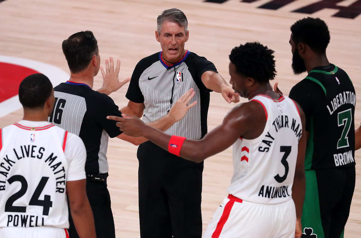 Players talk with an NBA referee