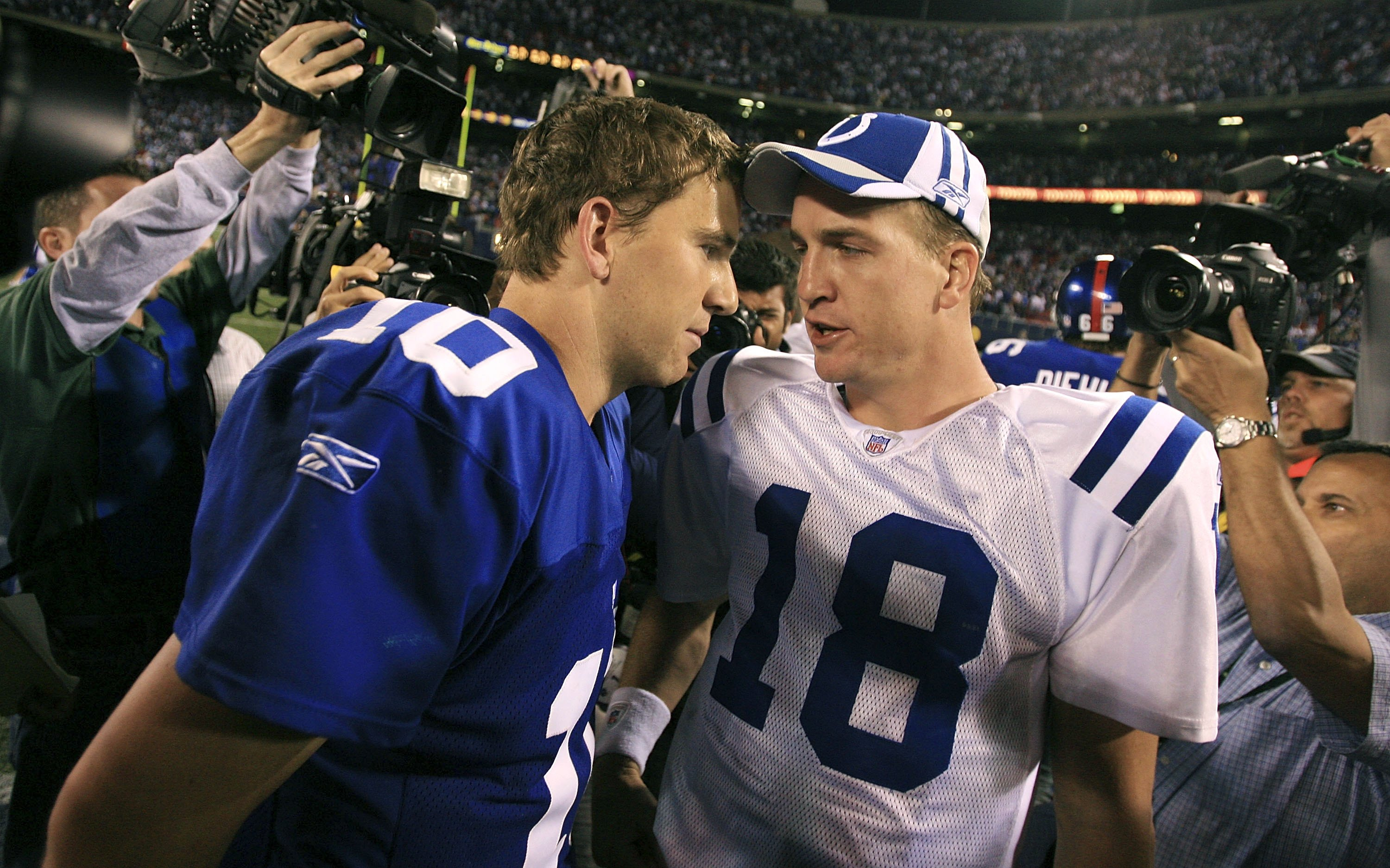 Eli and Peyton Manning talking after playing each other in an NFL game