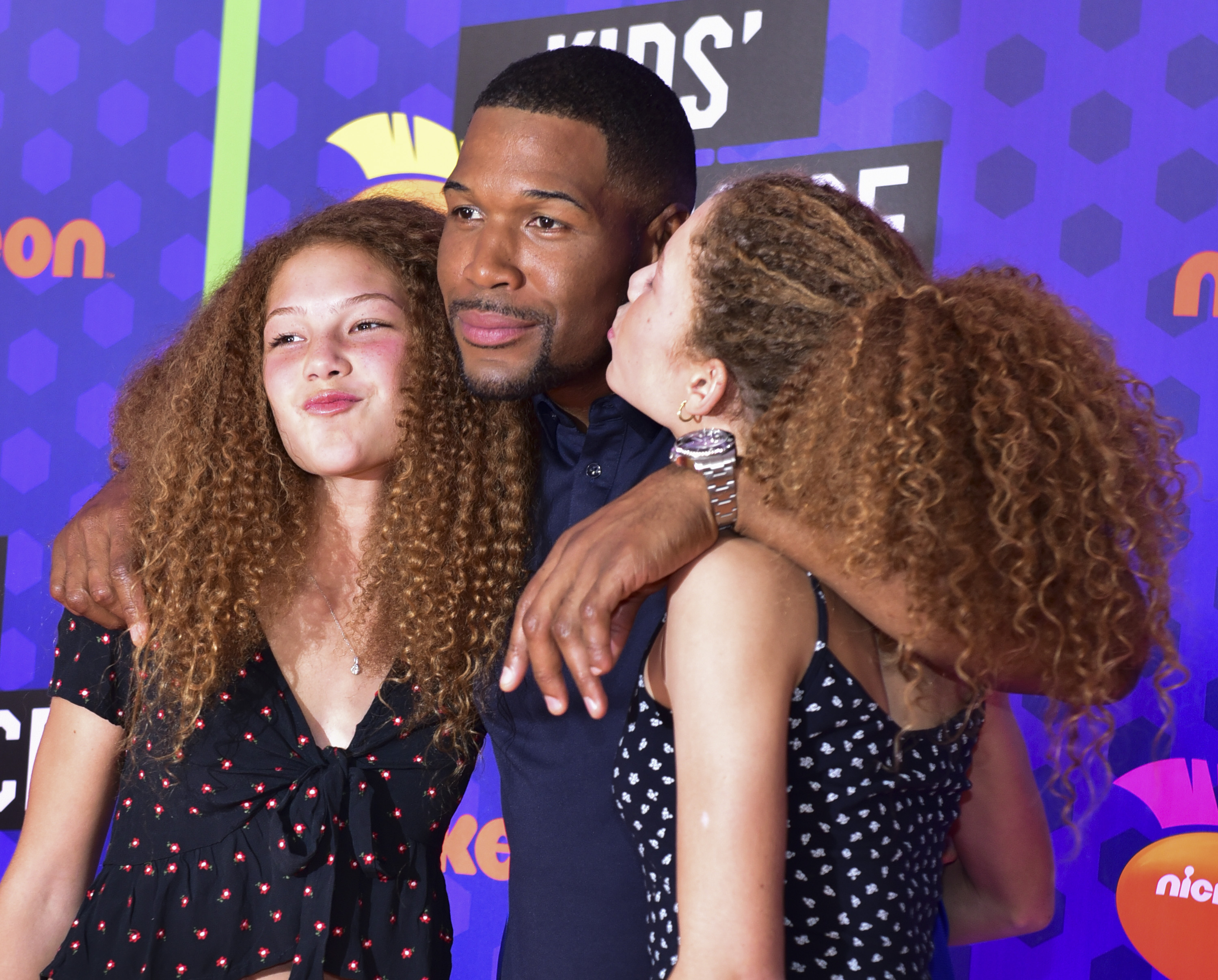 NFL player Michael Strahan with his twin daughters