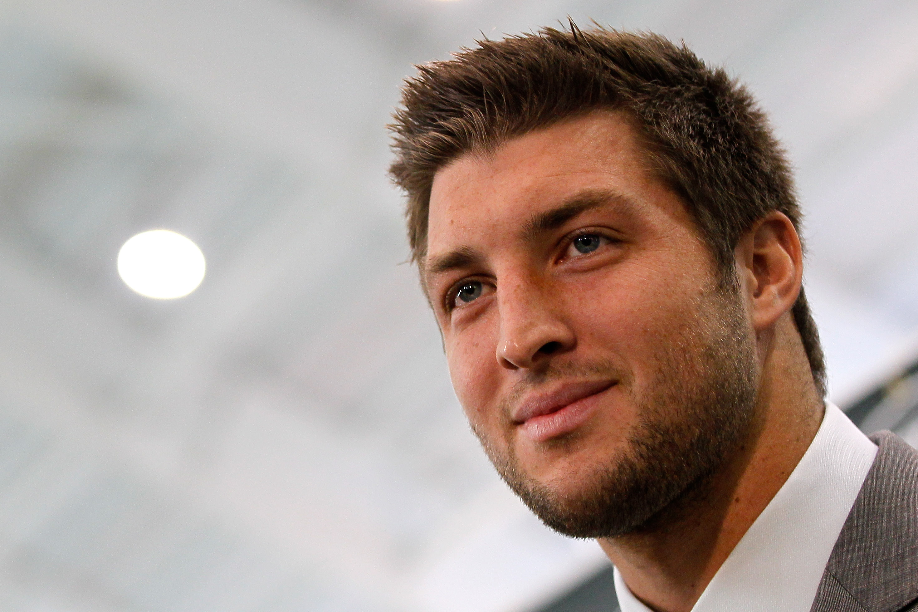 Tim Tebow looks on during a media interview