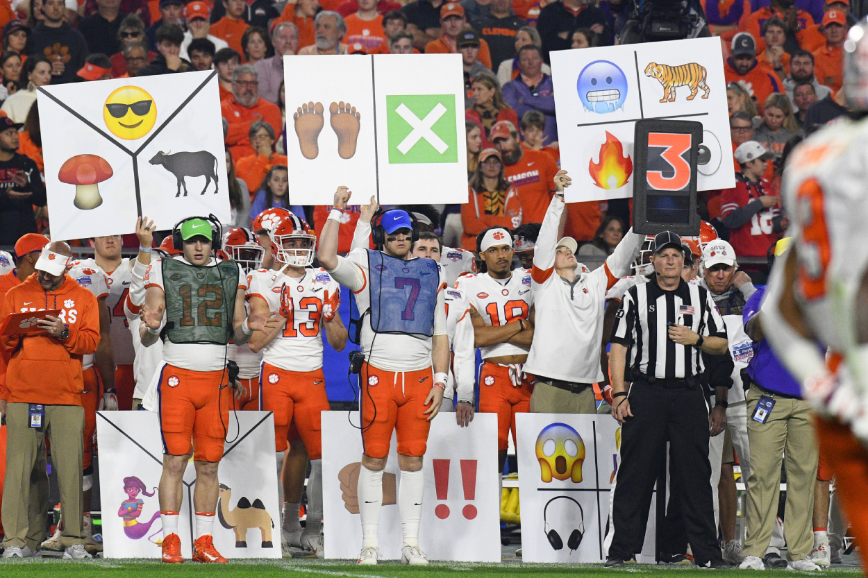 Players for Clemson hold up signs during a college football game
