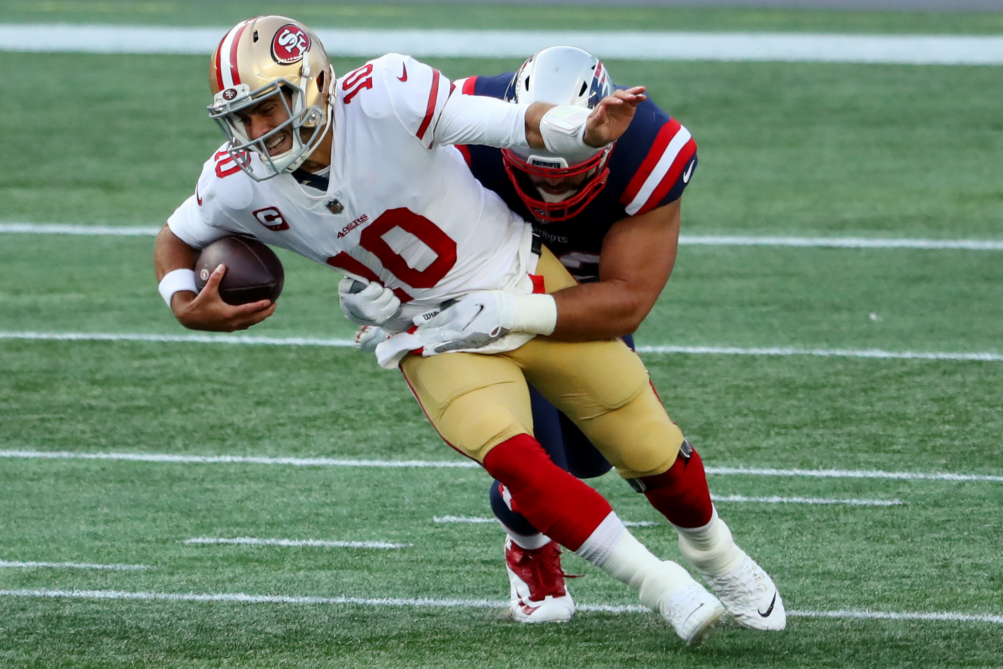 Jimmy Garoppolo of the San Francisco 49ers is tackled by Lawrence Guy