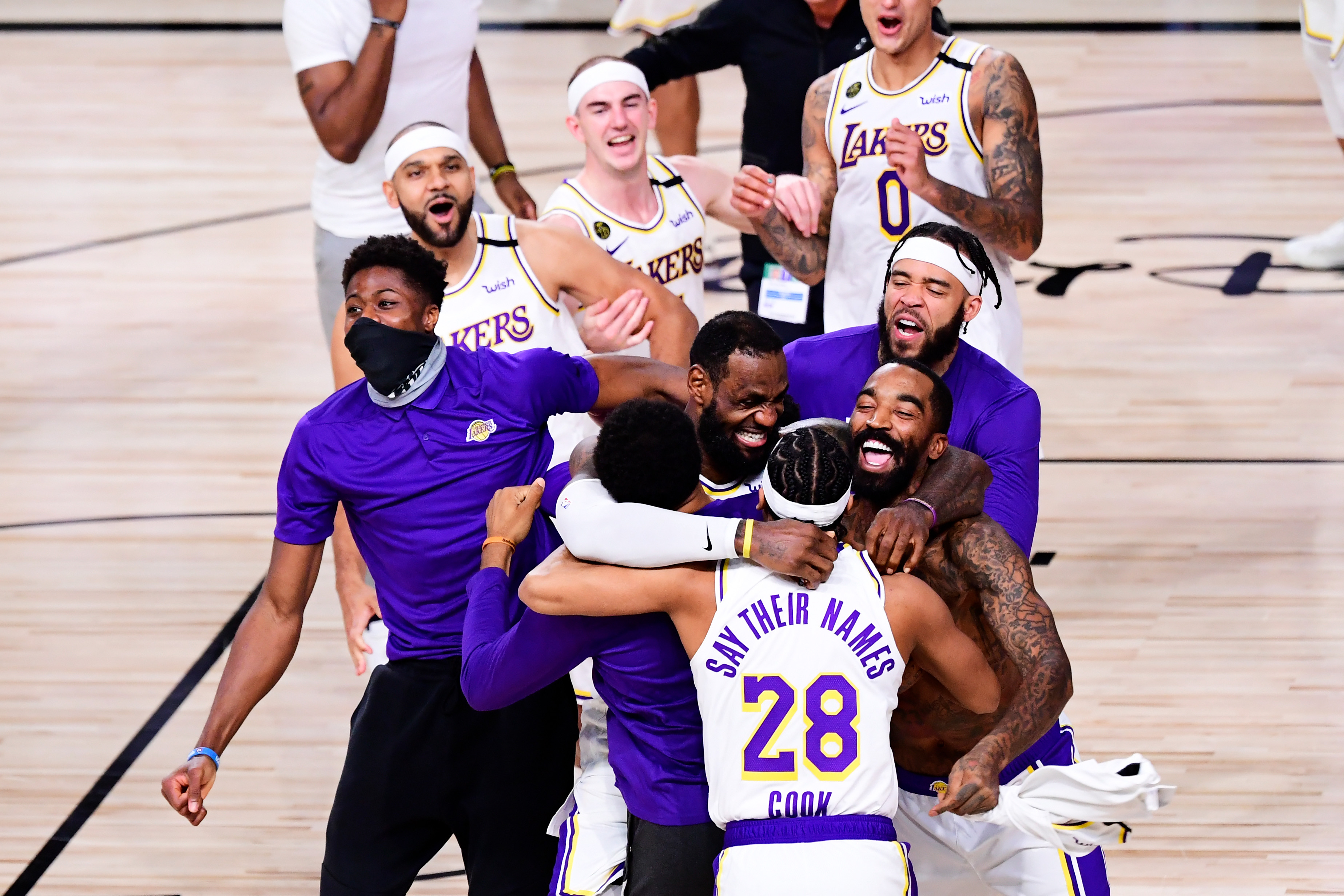 LeBron James and Quinn Cook celebrate with their Lakers teammates after winning the 2020 NBA Championship