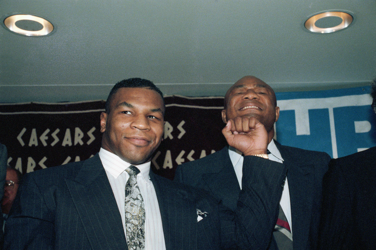 Former world heavyweight champions Mike Tyson (L) and George Foreman in 1990